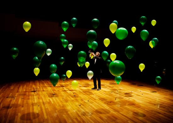 An illustration of Anderson localization. The green balloons represent disordered barriers that localize the sound of the trumpet at its source.