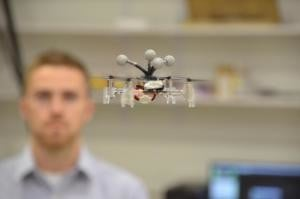 Grad student Mitchell Jones flys a mini drone in CSL's Intelligent Robotics Lab.
